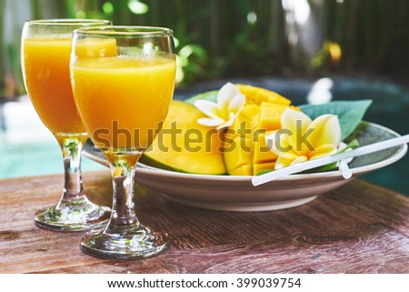 Glasses of fresh tropical smoothie or mango juice and fresh mango on a wooden table and tropical background. Soft focus. - stock photo