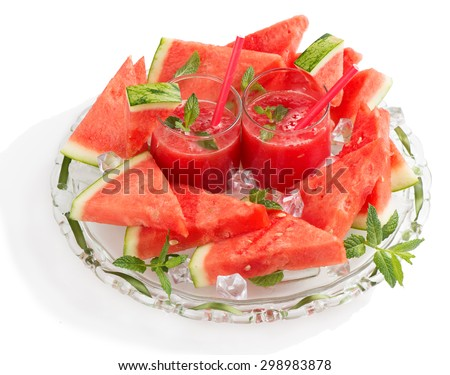 Glasses of fresh watermelon juice with mint leaves, i?e and sliced fruit isolated on white background