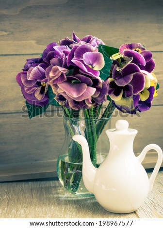 Glasses of green mint tea and vase with fresh violas on the table