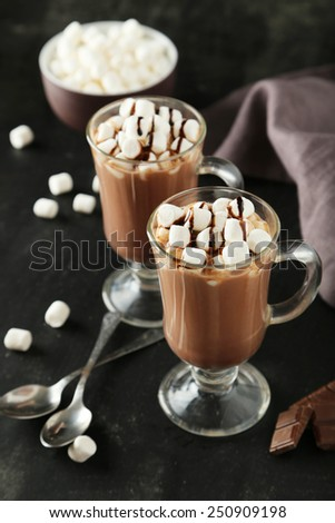 Glasses of hot chocolate with marshmallows on black background - stock photo