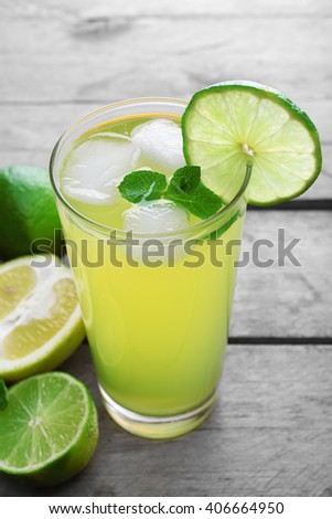 Glasses of lemon soda with ice and fresh mint on rustic wooden background - stock photo