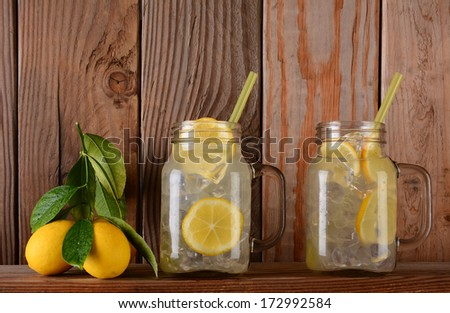 Glasses of lemonade  and lemons on a ledge in front of a rustic wooden kitchen wall. The mason jar style glasses have handles and drinking straws. - stock photo