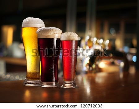 Glasses of light and dark beer on a pub background.