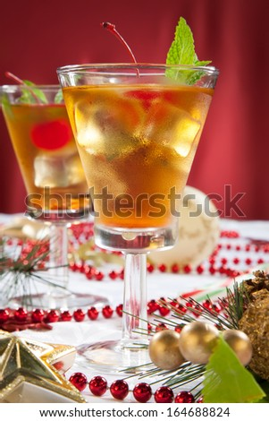 Glasses of Mint Manhattan cocktails surrounded with Christmas ornaments and decorations. Holiday cocktails series.  - stock photo
