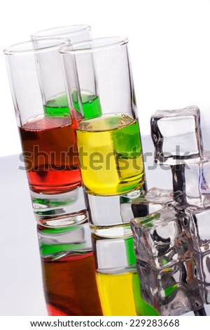 Glasses of multicolored alcohol drinks with ice - stock photo