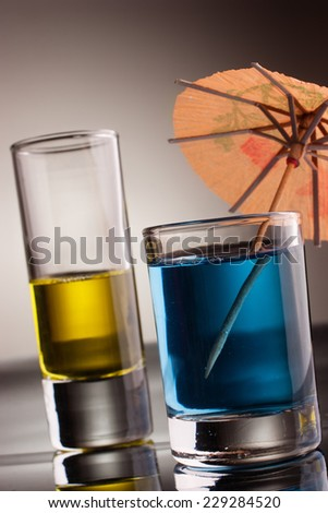 Glasses of multicolored alcohol drinks with reflection - stock photo