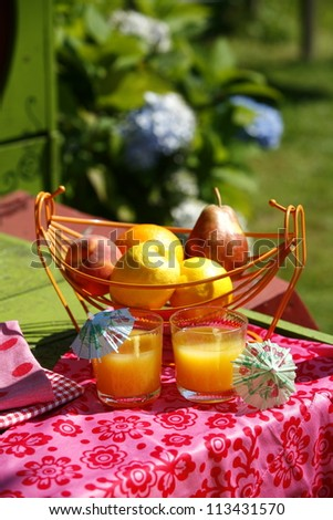 Glasses of orange juice and fruits on a table