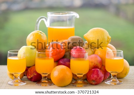 glasses of orange juice and lots of fruits on wooden table outdoor - stock photo