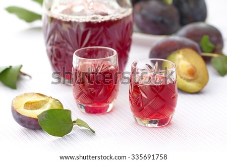 Glasses of plum alcohol with fresh plums  - stock photo