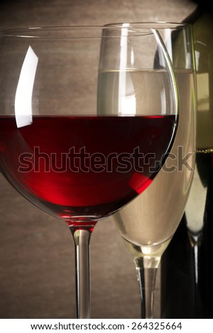 Glasses of red and white wine and bottle close-up on wooden background. Shallow DOF. - stock photo