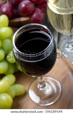 glasses of red and white wine and grapes, top view, close-up - stock photo