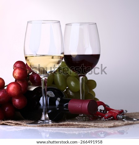Glasses of red and white wine, bottle and grape on light background - stock photo