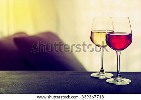 Glasses of red and white wine in a cozy living room, vintage color with text space - stock photo