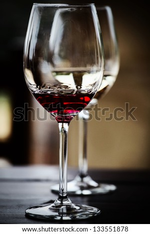 glasses of red and white wine on the table on a dark background - stock photo