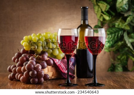 Glasses of red wine and bottle on wooden table