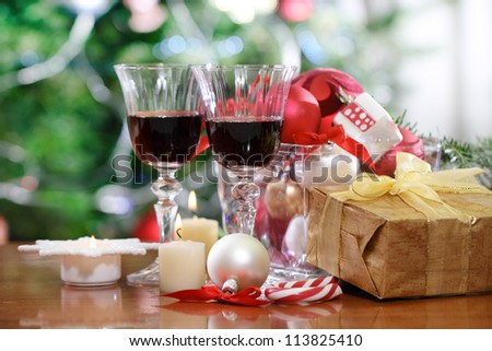 Glasses of red wine and Christmas decorations in front of Christmas tree for the holidays - stock photo
