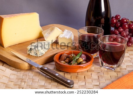 Glasses of red wine and mediterranean appetizers as italian antipasti or french starters �¢?? different kinds of cheese, olives and rosemary, two glasses of red table wine. - stock photo