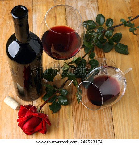 Glasses of red wine and red rose - stock photo