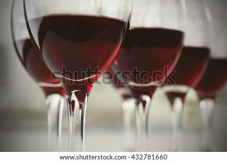 Glasses of red wine on white table closeup - stock photo