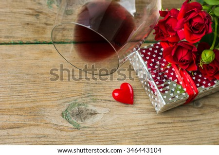 Glasses of red wine, present box and red roses for Valentines day celebration