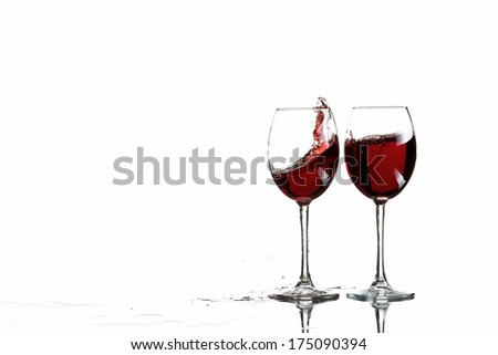 Glasses of red wine splash of white background reflection