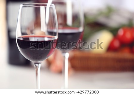 Glasses of red wine with food on table closeup - stock photo