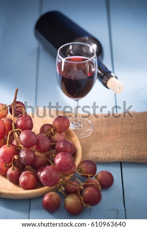 Glasses of red wine with red grapes and a bottle of wine on blue background