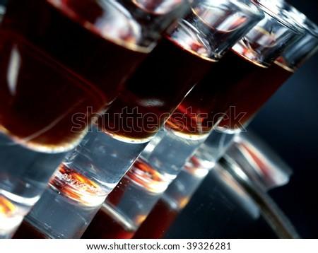 Glasses of shots on black background - stock photo