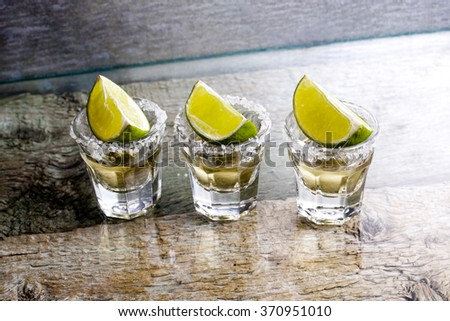 Glasses of silver and gold tequila with lime in a bar - stock photo