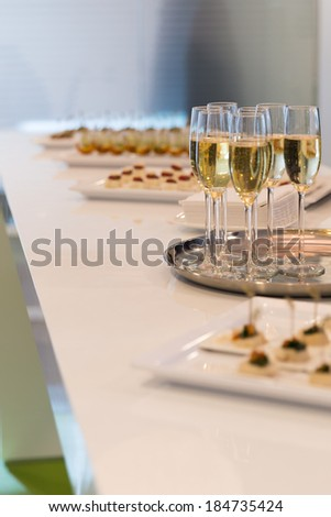 Glasses of sparkling champagne on a buffet table - stock photo
