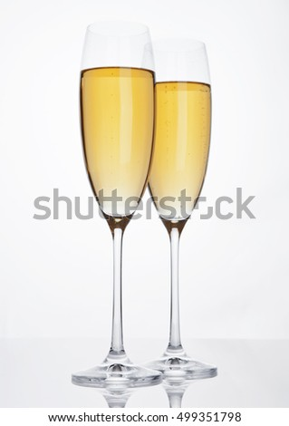 Glasses of sparkling champagne with bubbles on white background