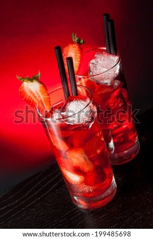 glasses of strawberry cocktail with ice on wood table and a red gradient background - stock photo