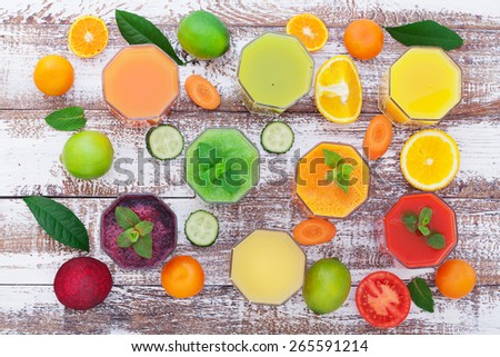Glasses of tasty fresh juice, on wooden desk. Unusual top view - stock photo