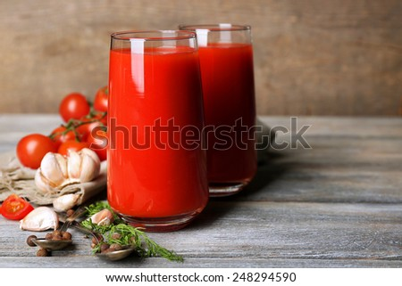 Glasses of tasty tomato juice and fresh tomatoes on wooden table - stock photo