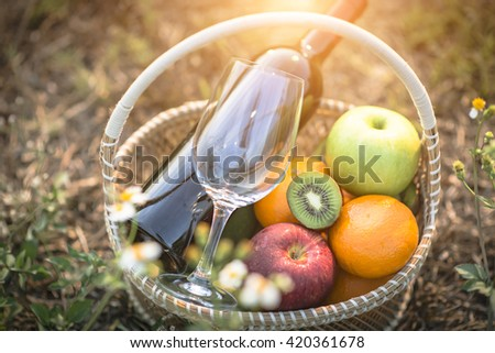 Glasses of the red wine on lawn summer picnic - stock photo