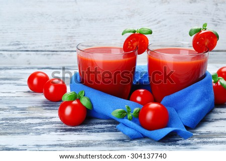 Glasses of tomato juice with vegetables on wooden background - stock photo