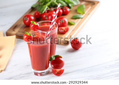 Glasses of tomato juice with vegetables on wooden table close up - stock photo