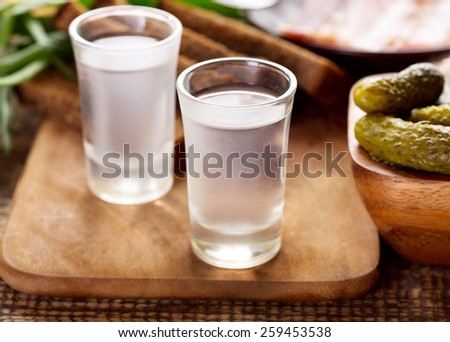 glasses of vodka with various snack on wooden table - stock photo