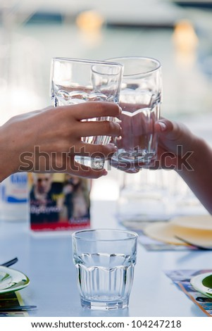 Glasses of water in graceful female hands