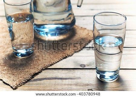 Glasses of water on a wooden table. Selective focus. Shallow DOF - stock photo