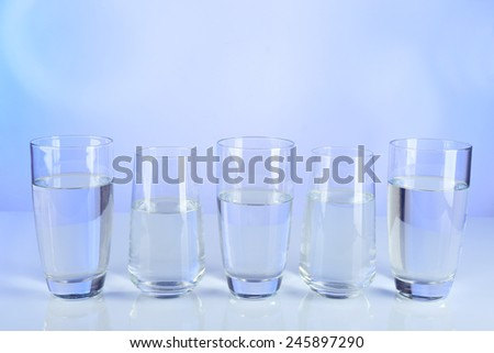 Glasses of water on table and colorful background - stock photo