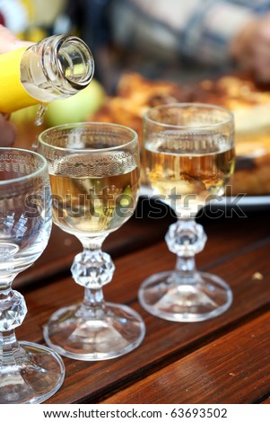 glasses of whiskey at the food covered wooden table. Shallow depth of field - stock photo