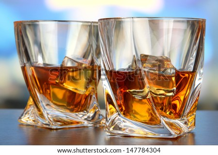 Glasses of whiskey, on bright background - stock photo