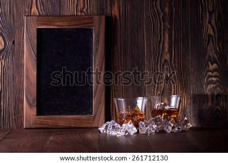 Glasses of whiskey on wood background - stock photo