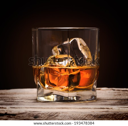 Glasses of whiskey with ice cubes on wood background - stock photo