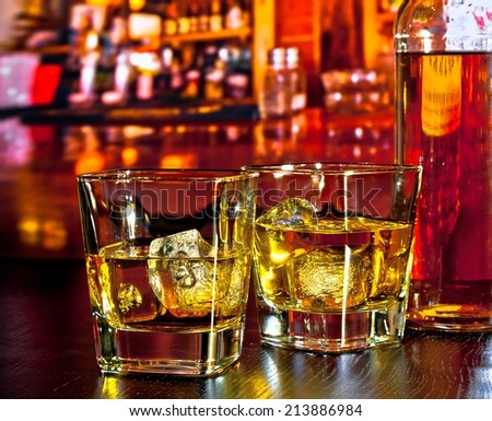 glasses of whiskey with ice on bar table near whiskey bottle on warm atmosphere lounge bar concept - stock photo