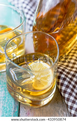 Glasses of whiskey with ice on wooden table
