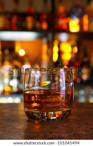 glasses of whisky on a dark wooden table in the background of light bar - stock photo