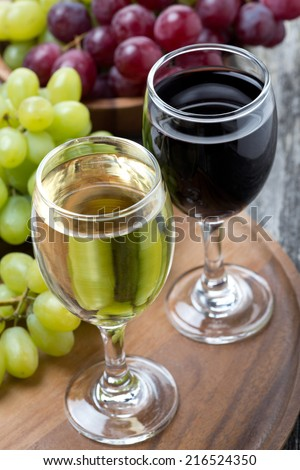 glasses of white and red wine, fresh grapes on a wooden board, top view, close-up - stock photo