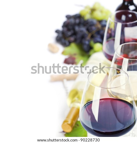 Glasses of white, red and rose wine and grapes over white - stock photo